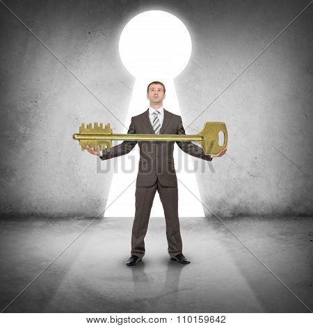 Businessman holding huge gold key