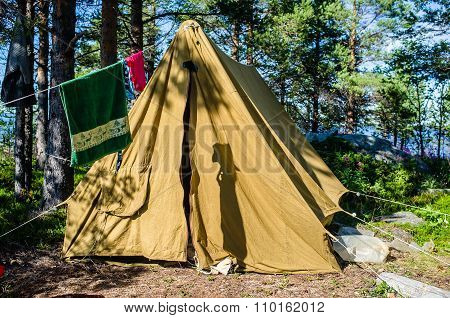 Old Canvas Tent Stands In A Pine Forest On The Island