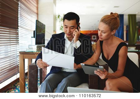 Attractive businesswoman using digital tablet during meeting with male partner