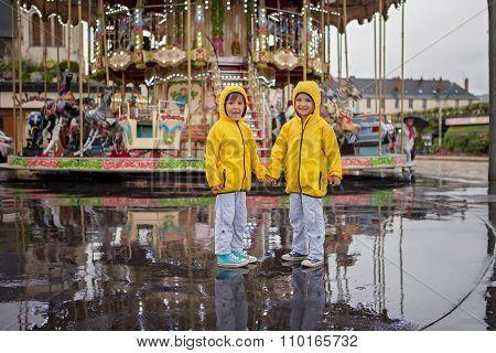 Two Sweet Children, Boy Brothers, Watching Carousel In The Rain, Wearing Yellow Raincoats