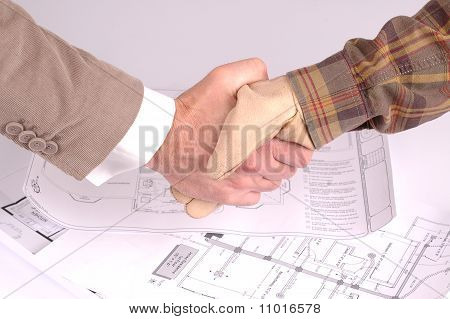 Worker And Businessman Shaking Hands Over House Renovation Plans