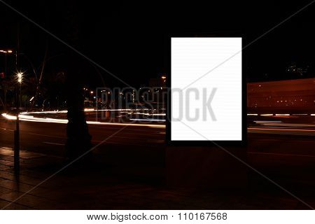 Public information board in urban setting at night