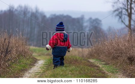 Child Walking In Countryside At Autumnal Bad Weather