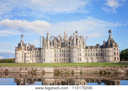 Chateau De Chambord, Royal Medieval French Castle With Reflection In The Water Canal In Front Of It
