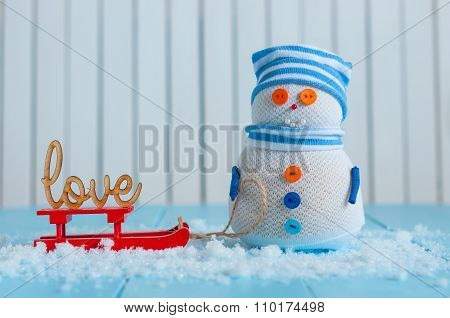 Snowman enjoying a sleigh ride with word LOVE. Handmade snowman stay With sledge and text love. Happ