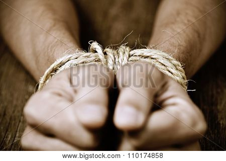 closeup of the hands of a young man tied with rope, as a symbol of oppression or repression, with a dramatic effect