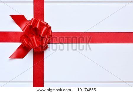 a red satin ribbon with a bow on a surface built of parallel white wooden slats
