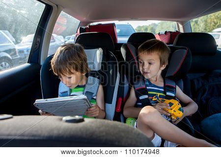 Two Boy In Children Car Seats, Traveling By Car And Playing With Toys And Tablet