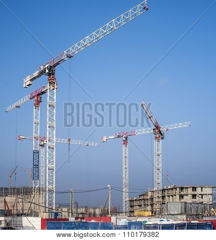 Construction Cranes On A Blue Sky Background