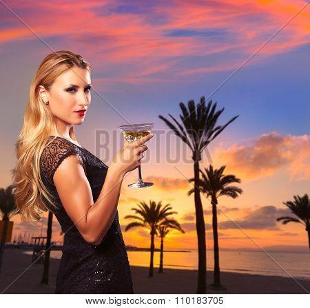 Blond tourist girl sunset in Arenal beach drinking vermouth Mallorca photomount
