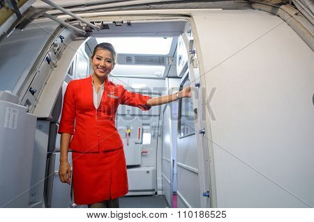 SINGAPORE - NOVEMBER 07, 2015: AirAsia crew member on board of Airbus A320. AirAsia is a Malaysian low-cost airline headquartered near Kuala Lumpur, Malaysia