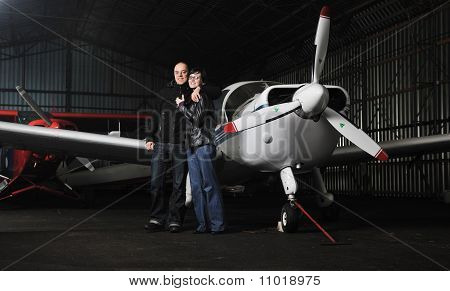 Happy Young Couple Posing In Front Of Private Airplane
