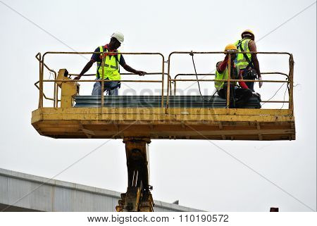 Three workers standing in the mobile crane basket