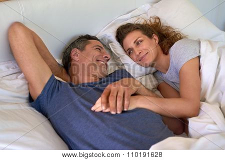 Mature caucasian cheerful couple lying in a bed, happy smiling looking to each other, holding hands