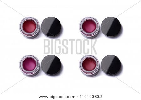 Red shade lip glosses in jars, top view isolated on white background