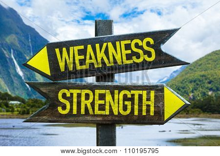 Weakness - Strength signpost with mountains background