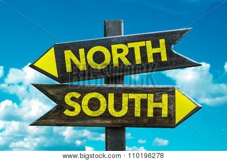 North - South signpost with sky background