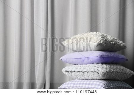 Multicoloured pillows on a curtain background