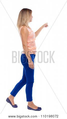back view of pointing walking  woman. going girl pointing.  backside view of person.  . Isolated over white background. blonde in blue pants is holding up his left hand to the right.