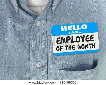 Employee of the Month words written on a nametag worn by a worker or top staff member in a blue shirt