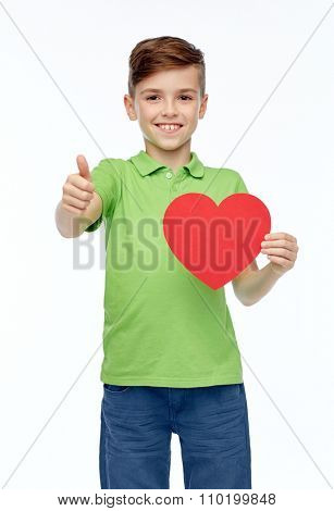childhood, love, charity, health care and people concept - happy smiling boy in green polo t-shirt holding blank red heart shape and showing thumbs up