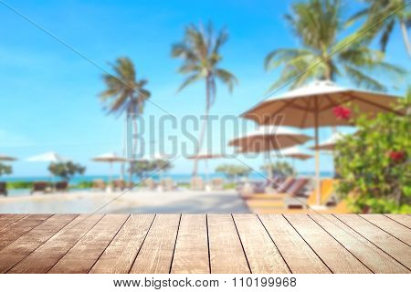 Wooden Table With Blurry Tropical Sea And Resort Background.