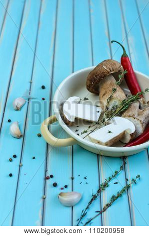 Fresh porcini mushrooms and herbs in frying pan on wooden table