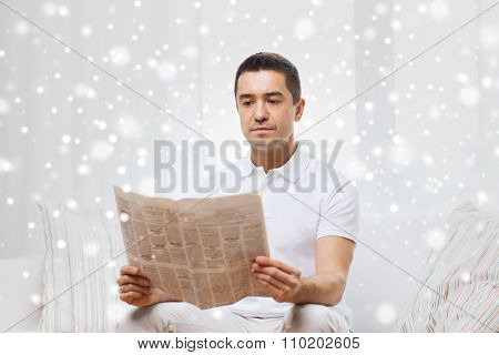 leisure, information, people and mass media concept - man reading newspaper at home over snow effect