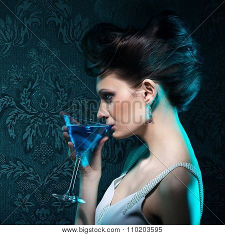 Young woman with martini glass in blue light on damask wallpaper background