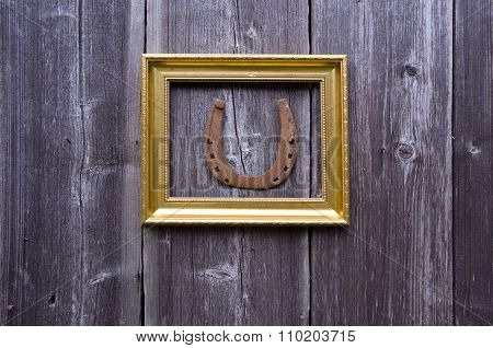 Golden Ornate Frame With A Horseshoe On Wooden Wall