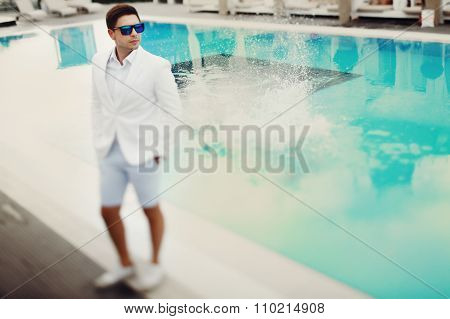 Handsome Confident Groom In Sunglasses And White Suit Posing Near A Pool At Resort