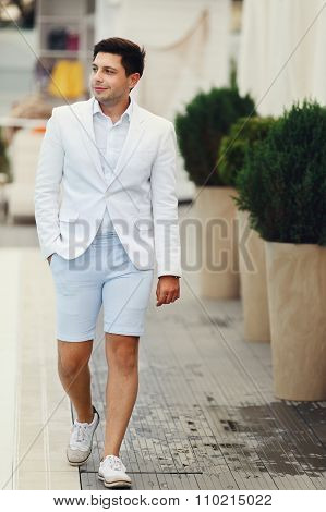 Handsome Confident Groom In White Suit Walking Near Pool At Resort