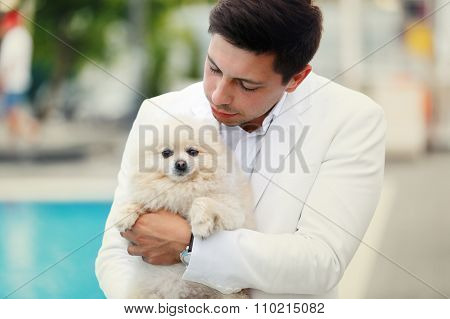 Happy Smiling Handsome Groom In White Suit Holding Dog Near Pool