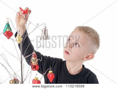 Child Is Concentration About Decorating Metal Wire Christmas Tree, With Glass Ornaments
