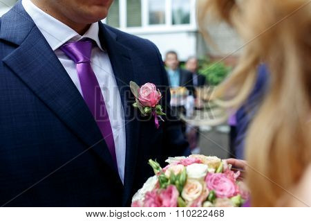 Stylish Groom In A Dark Blue Suit With A Pink Rose Boutonniere Close-up