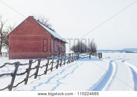 Old barn and fresh car tracks in snow