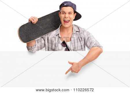 Cocky young skater standing behind a blank signboard and pointing on it with his hand isolated on white background
