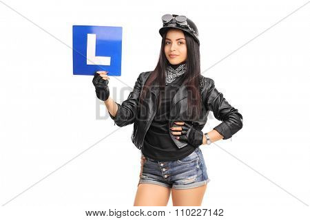 Studio shot of an attractive female biker holding an L-sign and looking at the camera isolated on white background