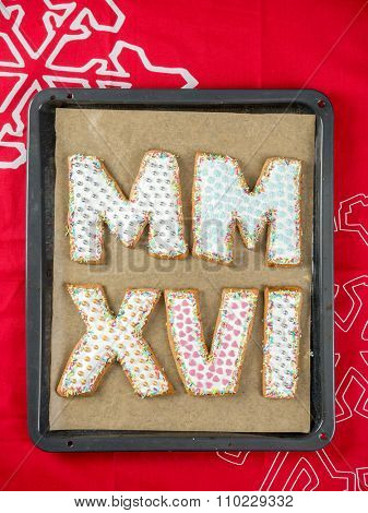 Home-made gingerbread cookies in shape of Roman numerals representing 2016 New Year date on baking tray