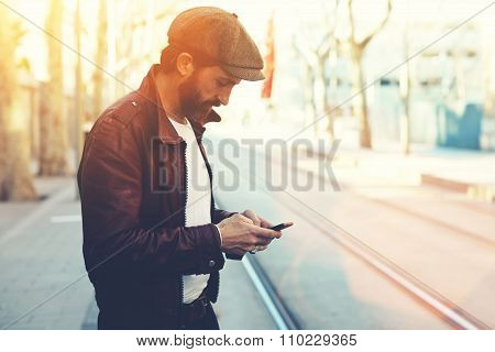 Bearded male with retro style using cell telephone while standing in urban setting