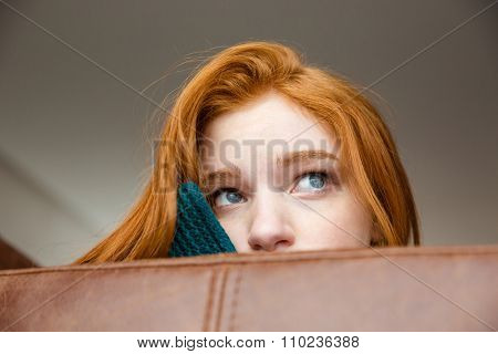Unconfident shy redhead girl peeping over brown leather sofa and looking away