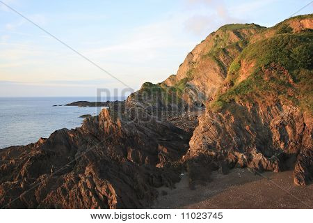 Rocky Headland And A Small Pebble Beach Bathed In Evening Sunlight