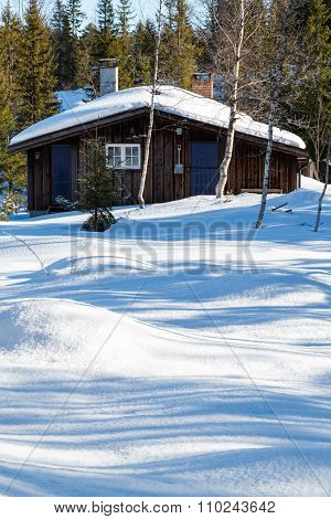 Typical Black Norwegian Cabin Surrounded By Snow In The Forest