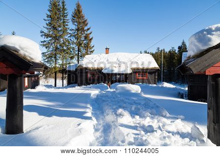 Typical Black Norwegian Cabin Surrounded By Deep Snow In The Forest
