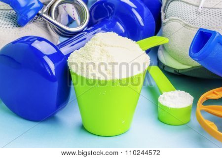 Scoops with whey protein and creatine with sport items around