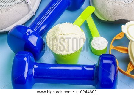 Scoops with pure whey protein and creatine with sport items around
