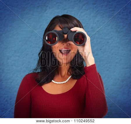 Business woman with binoculars over blue abstract background.
