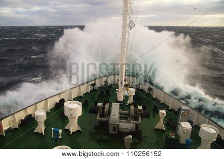 Big wave rolling over the snout of the ship. Nautical background