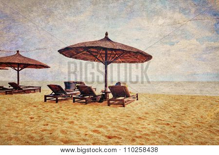 Woman relaxing and reading a book under umbrella on white sand beach at Phu Quoc island in Vietnam. Retro and grunge style. A person is not recognizable