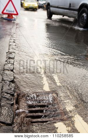 Water Pouring Down Drain On Flooded Road
